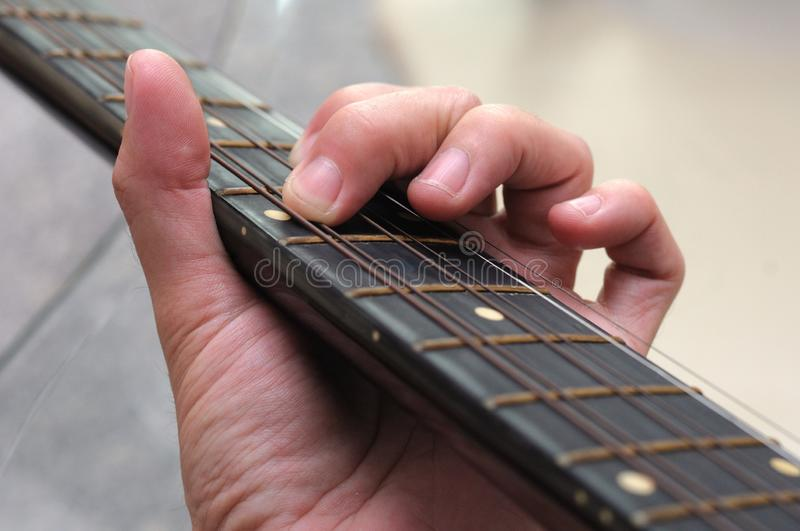A closeup photo of the left hand fingers of a guitarist playing an acoustic guitar stock photo