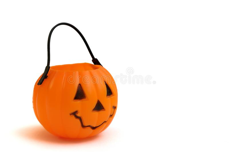 A plastic Halloween cup in the shape of a pumpkin with a face features. A closeup photo taken on a plastic Halloween cup in the shape of a pumpkin with a face stock photography