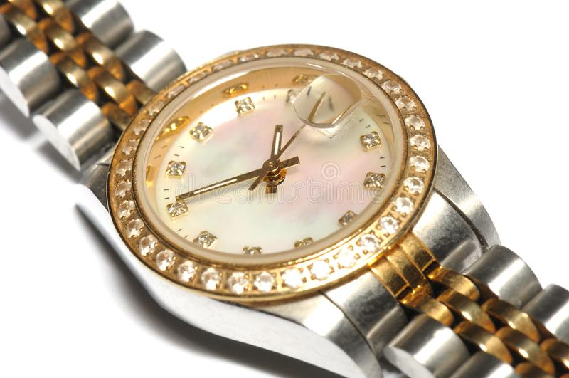 A silver ladies watch with a round watch face and diamonds on the rim royalty free stock image