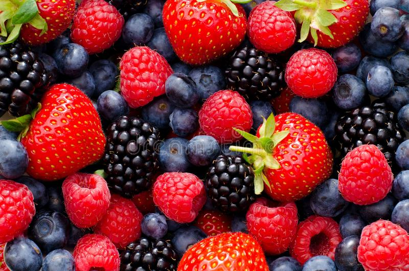 Closeup photo of wild berries strawberries, raspberries, blackberries, blueberries royalty free stock image