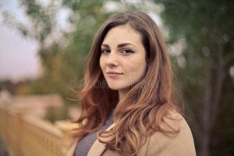 Closeup Photo of Woman With Brown Coat and Gray Top stock photo