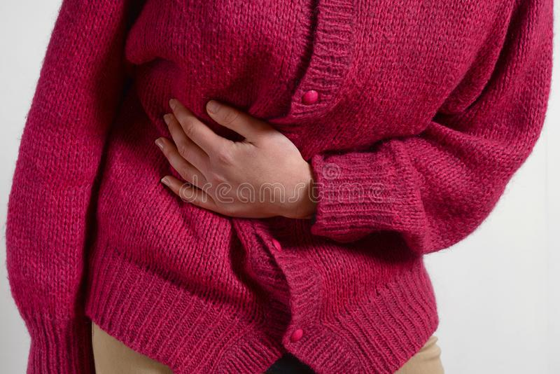 Closeup photo. a woman has a pain in her stomach, and holds her hands. Concept of female medicine. Digestive problems, gynecology stock image