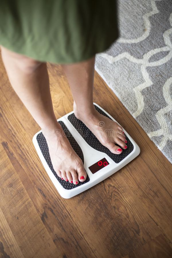 Closeup photo of a Woman standing on a digital weight scale stock image