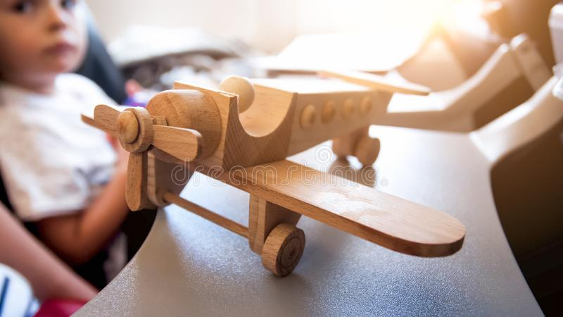 Closeup image of wooden toy plane in airplane against sun shining through illuminator. Closeup photo of wooden toy plane in airplane against sun shining through stock photos