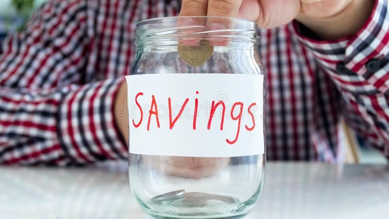 Closeup image of young man putting golden coin in glass jar for money savings stock images