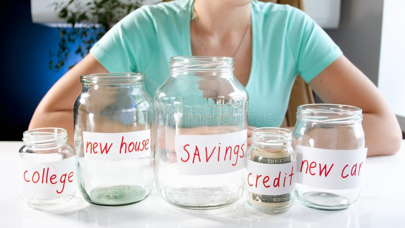 Closeup photo of young woman and different glass jars for investing money royalty free stock image