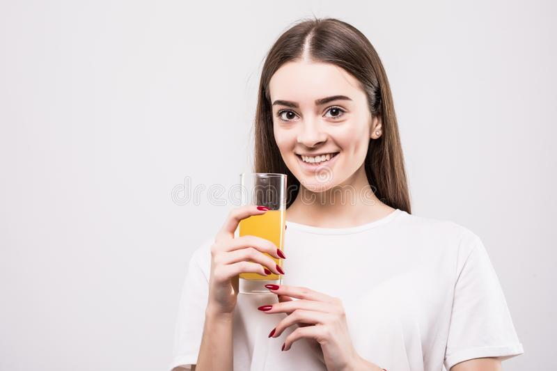 Young woman drinking orange juice. Beautiful face of woman close up with glass of orange juice on white background. Healt. Closeup photo of young woman drinking stock images