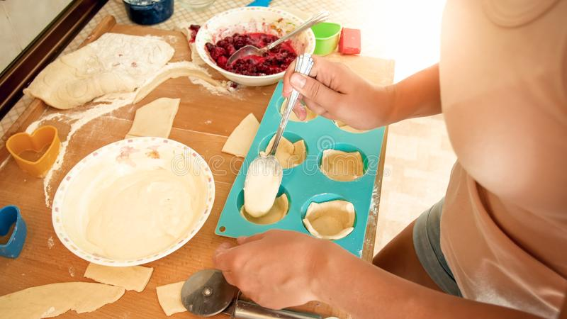 Closeup image of young woman making cupcakes. Girl putting creme inside of the dough in silicone forms for baking stock photography