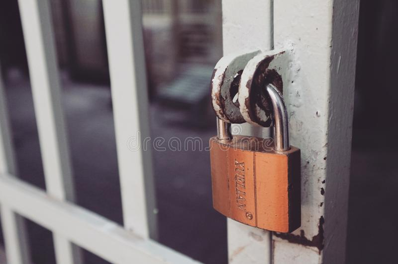 Closeup Photography of White Gate With Brass-colored Padlock stock photo