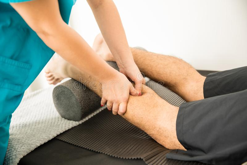 Physiotherapist Hands Massaging Calf Muscle Of Patient. Closeup of physiotherapist hands massaging calf muscle of patient in hospital royalty free stock photo