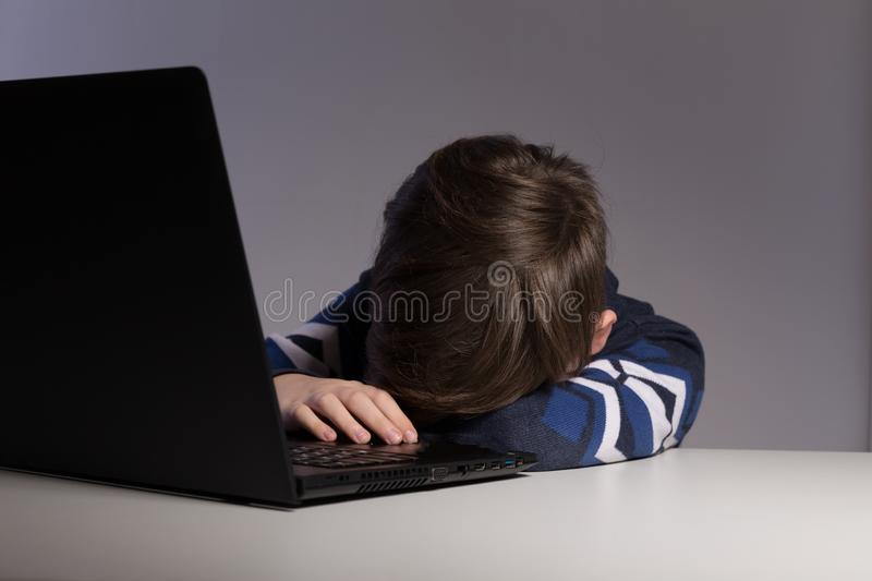 Closeup picture of bullying teen boy feeling upset infront of computer. Stressed sad boy is bullying by his classmates. Closeup picture of bullying teen boy royalty free stock photography