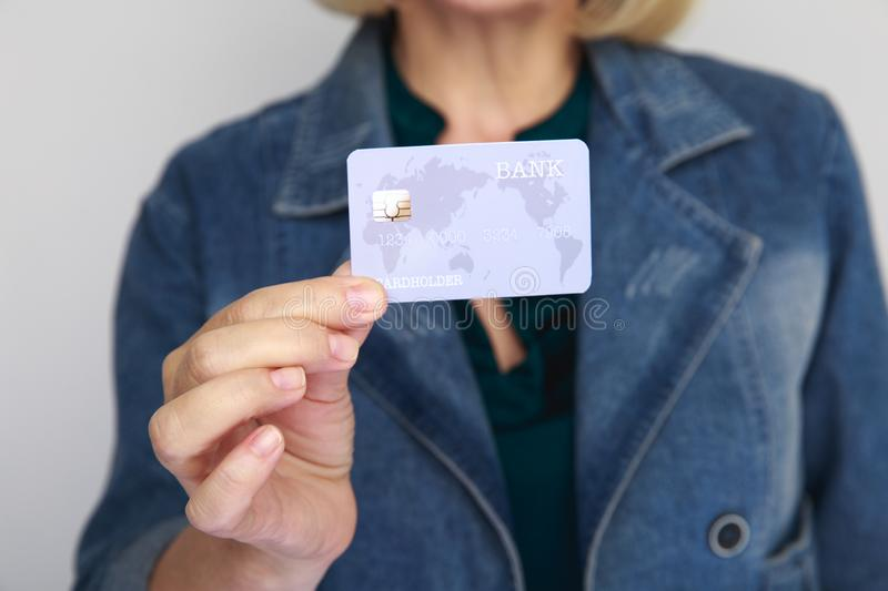 Closeup picture of credit card in a woman`s hand isolated in a studio. stock photography