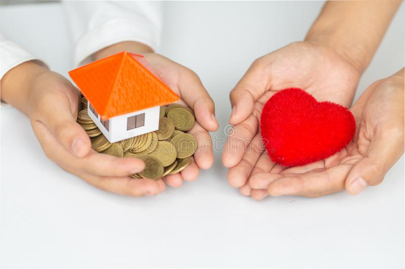 Closeup picture of female hands holding model house and red heart. charity, real estate and family home concept stock photo