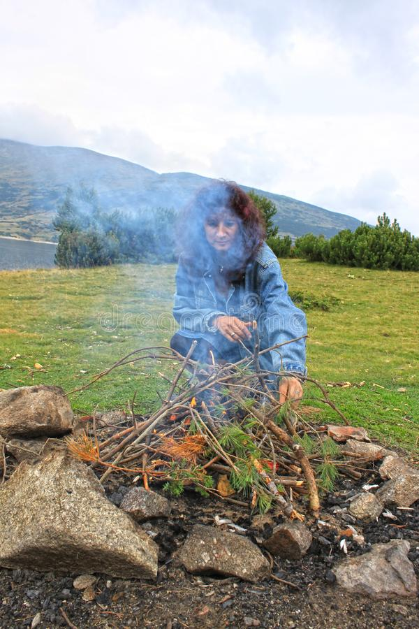 A great picnic fire in the wood and a woman near it royalty free stock photo