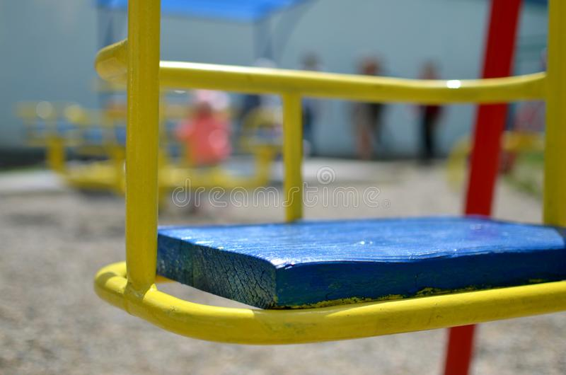 Closeup picture of an iron empty swing in the playground with silhouettes of children royalty free stock image