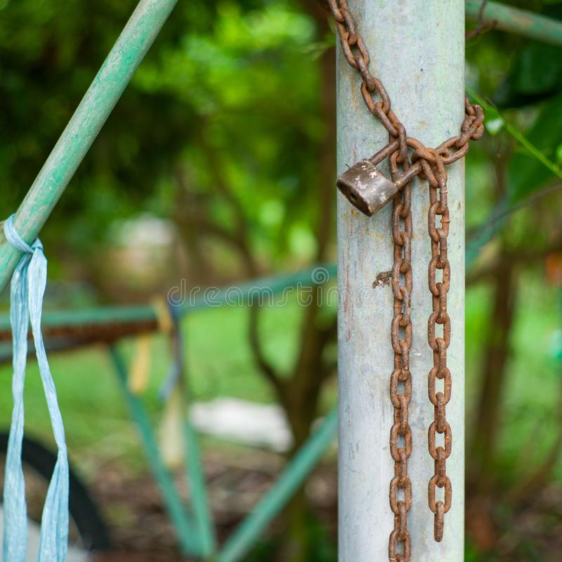 Free Closeup Picture Of Rusted Lock And Chain On The Steel Column With Blurred Bokeh Background. Love And Commitment Concept Stock Photos - 134180023