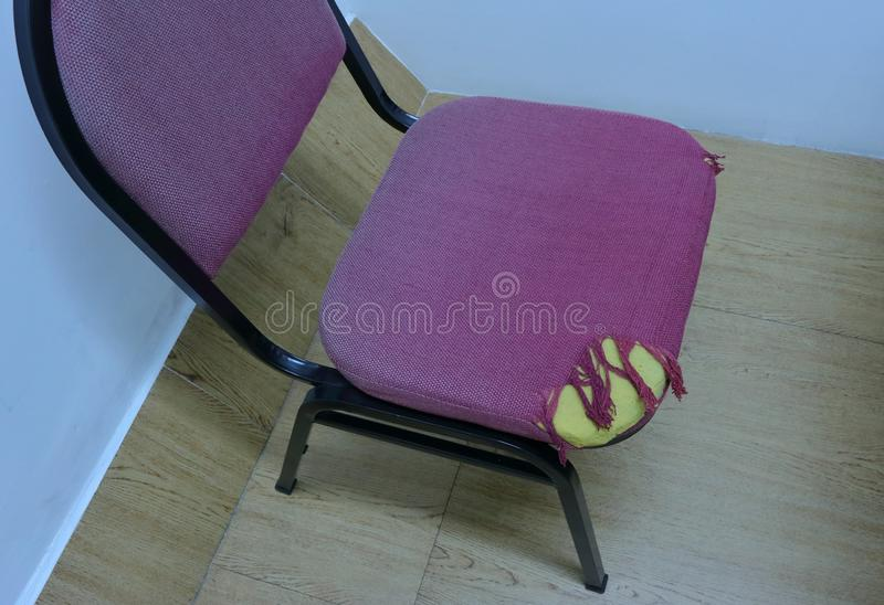 A torn cloth chair. Closeup picture of a torn cloth chair in a room royalty free stock image