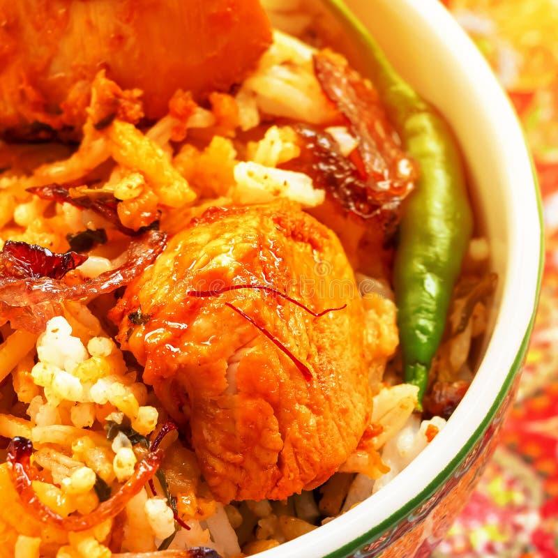 Closeup piece of chicken tikka and saffron strands Indian Biryani served stock image