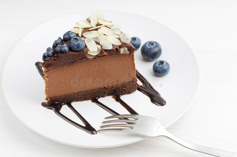 Closeup piece of homemade chocolate cheesecake with blueberries and almond slices royalty free stock photo