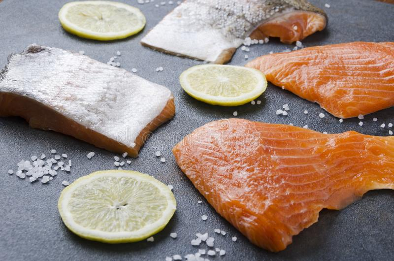 Tasty several pieces of salmon with lemon,seasalt on grey table.Cooking preparation royalty free stock photos