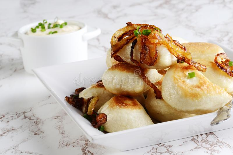 Pierogies with caramelized onions on a plate. Closeup of pierogies with caramelized onions on a plate stock photos