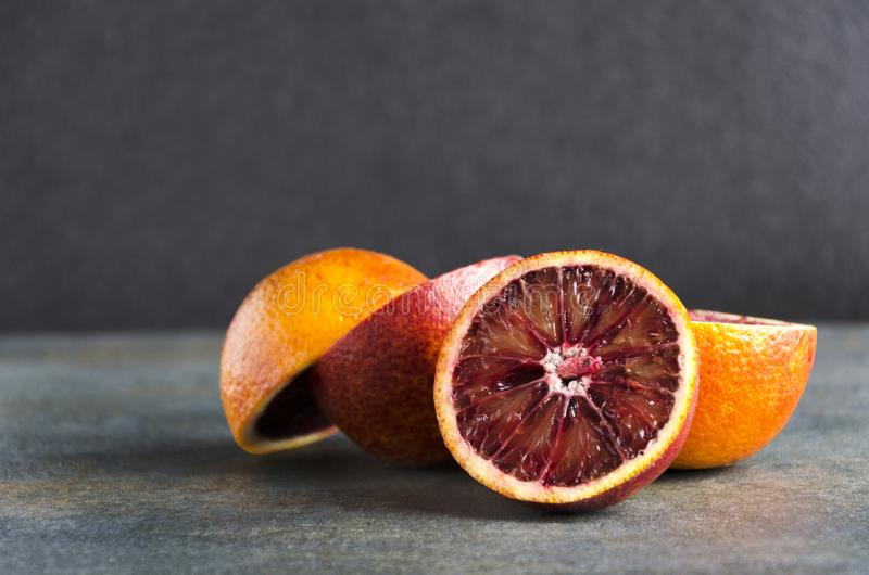 Closeup of pile of blood orange on the grey surface against black background stock images