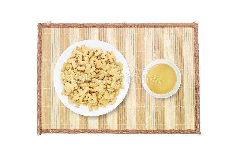 Closeup pile of brown biscuit in english alphabet on white dish and brown tea in white ceramic cup on wood mat isolated on white b stock photos
