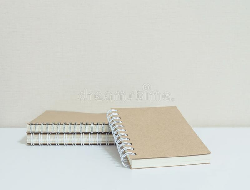 Closeup pile of brown note book on white desk and wallpaper in room textured background with copy space. Closeup pile of brown note book on desk and wallpaper in stock photo