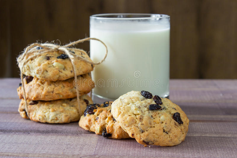 Closeup of pile made from homemade moms chocolate cookies and glass of milk. On wooden background stock photography