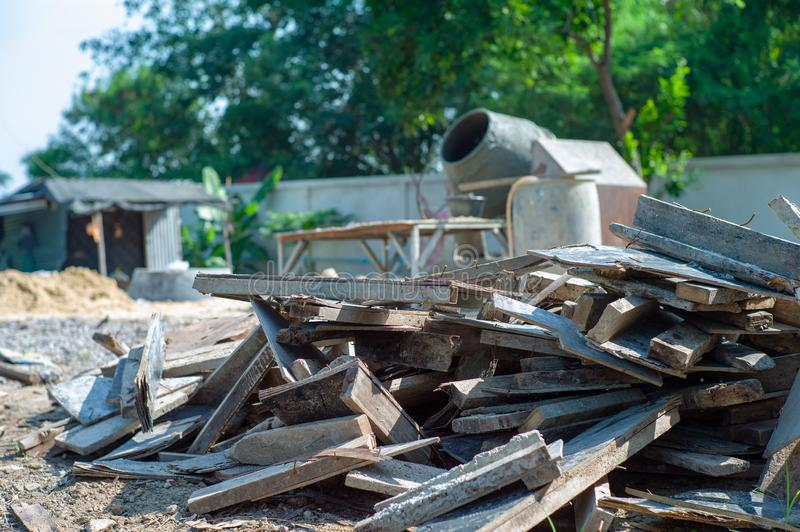 Closeup pile of useless wood at the construction site with blurred concrete mixer in background.  stock image