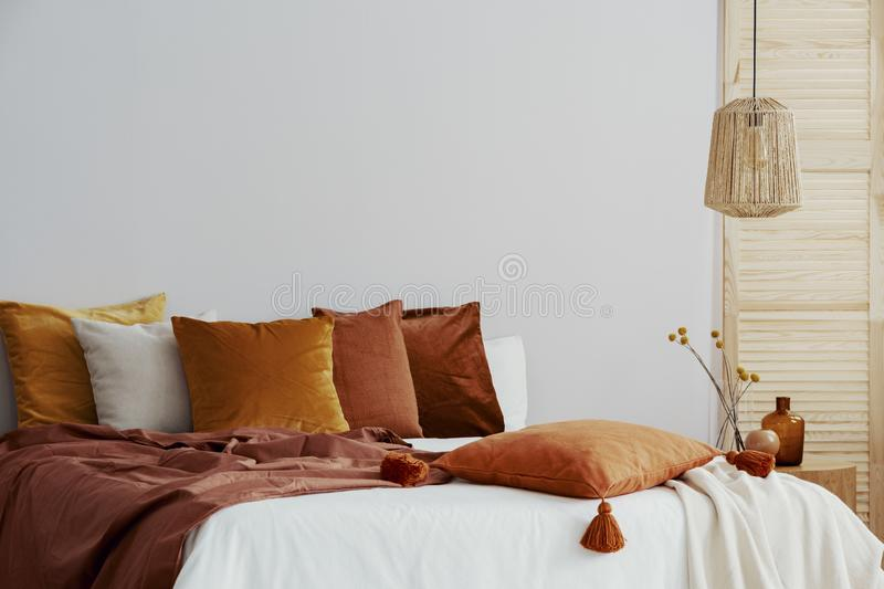 Closeup of pillows and blanket on cozy bed with white duvet royalty free stock images