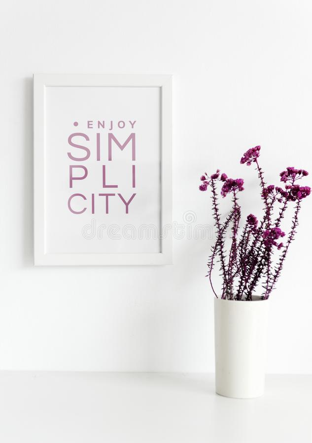 Closeup of pink flowers in white vase with photo frame on wall stock image