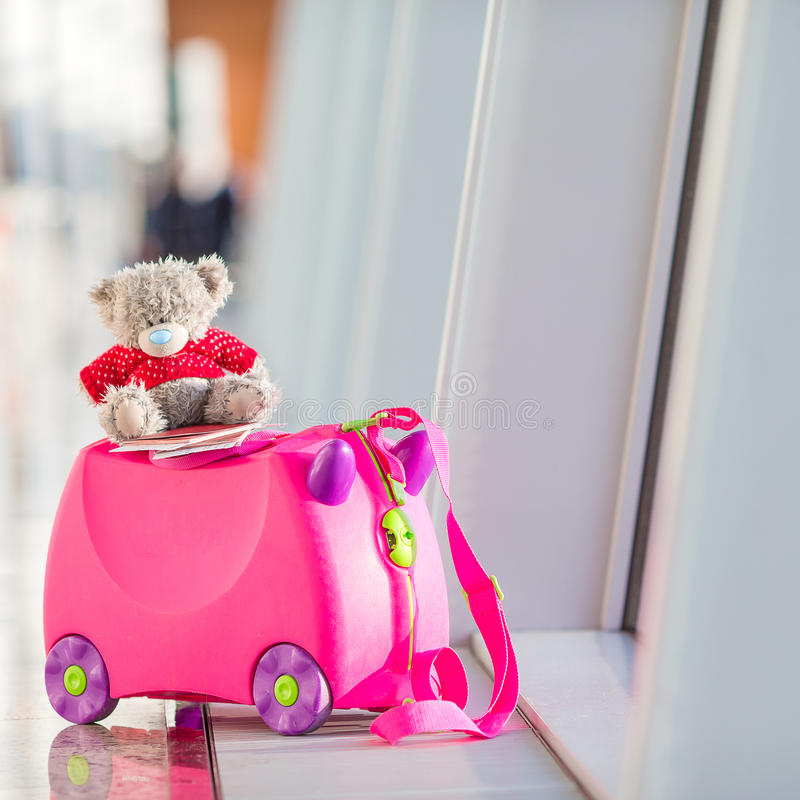 Closeup pink small kids suitcase in airport near royalty free stock images