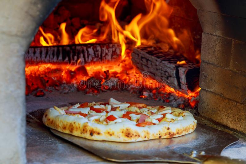 Closeup pizza in firewood oven with flame behind. Close up pizza in firewood oven with flame behind stock photography