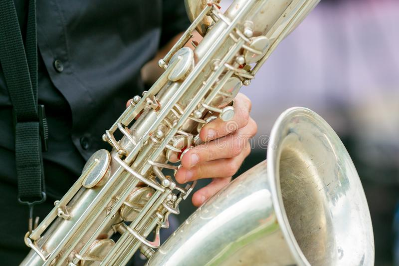 A closeup plane of saxophone in hands of sax player royalty free stock photos