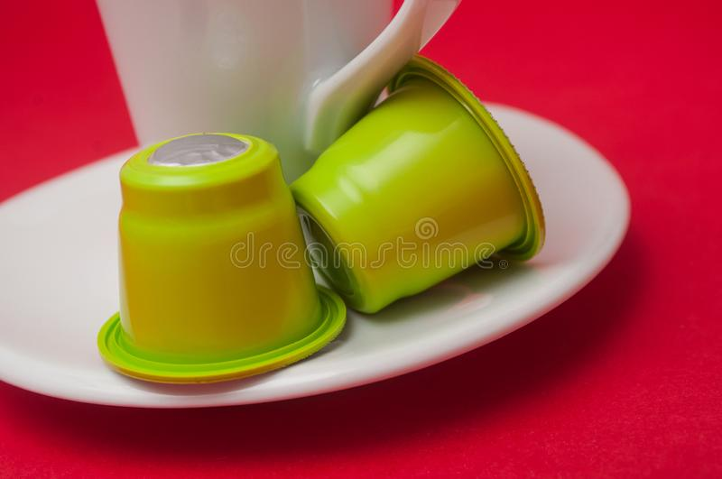 plastic espresso coffee capsules on white cup of coffee on red background royalty free stock image