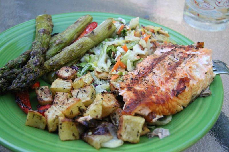 Closeup on plate grilled vegetables and salmon fillet asparagus and onions potatoes stock image