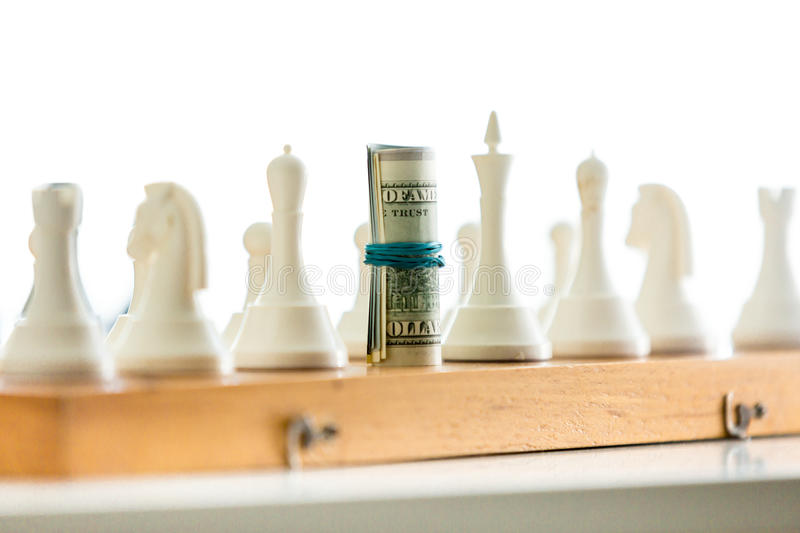 Closeup of playing in chess with twisted banknotes royalty free stock image