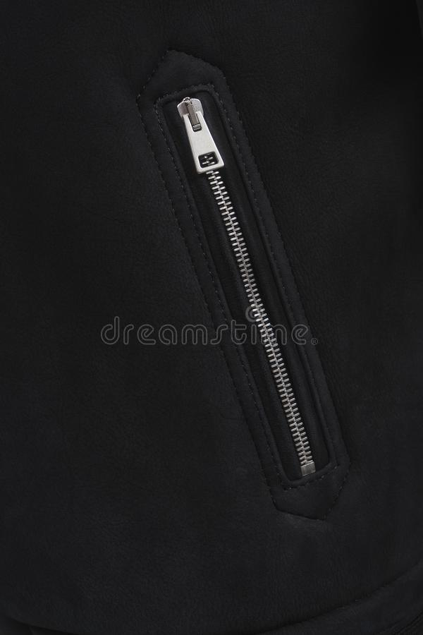 Closeup of a pocket on a metal zipper. Black leather winter jacket on a clasp. Clothes texture. Closed pocket royalty free stock image