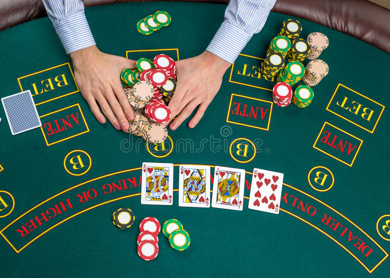 Closeup of poker player with playing cards and chips stock image
