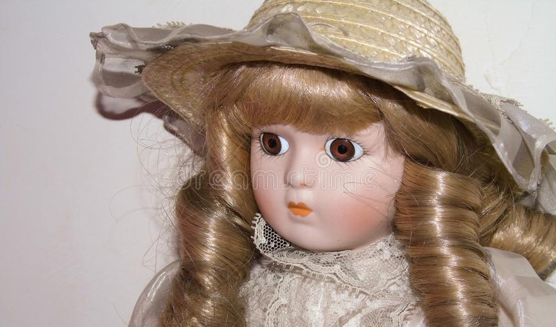 Closeup of a blonde porcelain doll, vintage toys on white background stock photography