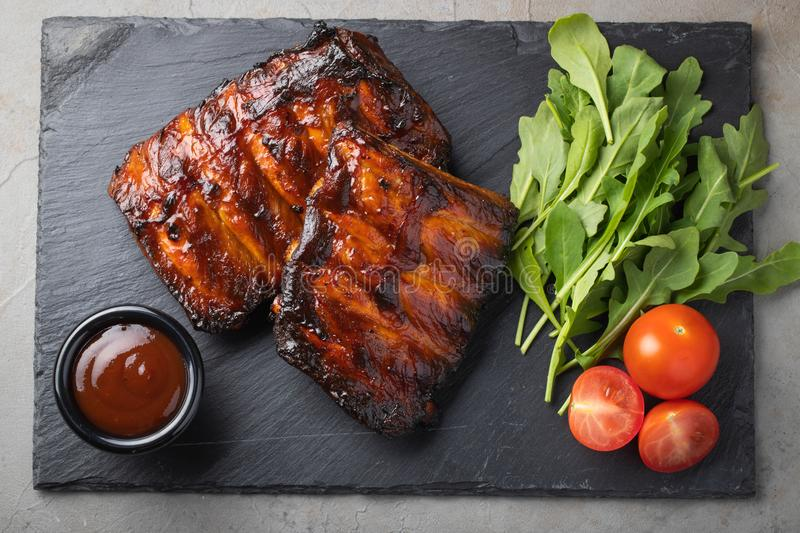 Closeup of pork ribs grilled with BBQ sauce and arugula. Tasty snack to beer on a stone Board for filing on old concrete. Background. Top view stock photos