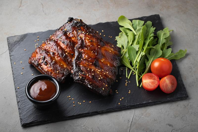 Closeup of pork ribs grilled with BBQ sauce and arugula. Tasty snack to beer on a stone Board for filing on old concrete. Background. Top view stock photo