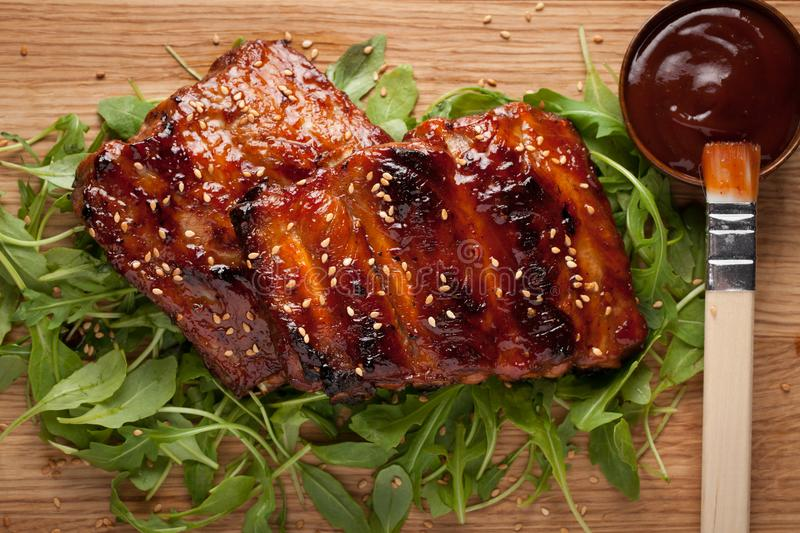 Closeup of pork ribs grilled with BBQ sauce and caramelized in honey on a bed of arugula. Tasty snack to beer on a stock photos