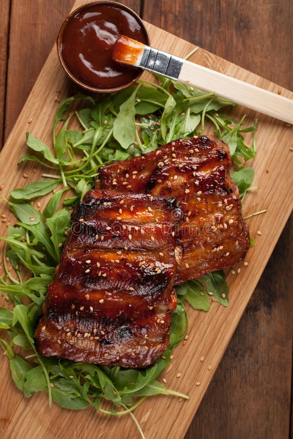 Closeup of pork ribs grilled with BBQ sauce and caramelized in honey on a bed of arugula. Tasty snack to beer on a. Wooden Board for submission on the old stock photo