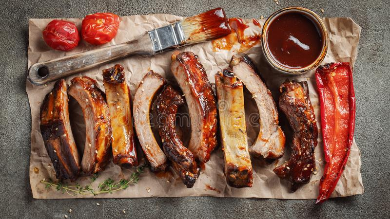 Closeup of pork ribs grilled with BBQ sauce and caramelized in honey. Tasty snack to beer on a paper for filing on dark concrete. Background. Top view. Flat lay royalty free stock photography