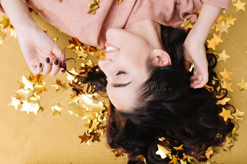 Closeup portrait from above young joyful woman with cut curly hair having fun in golden tinsels on couch at home. Lovely royalty free stock photo