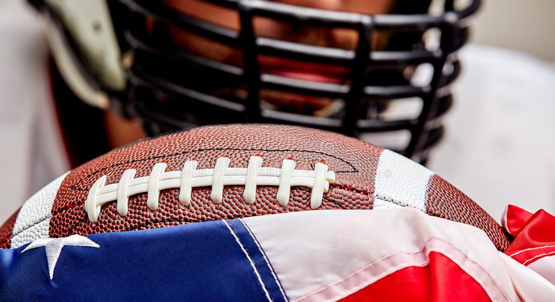 Closeup portrait of an aggressive American football player. Aggressive player bites his ball. The concept of American royalty free stock photography