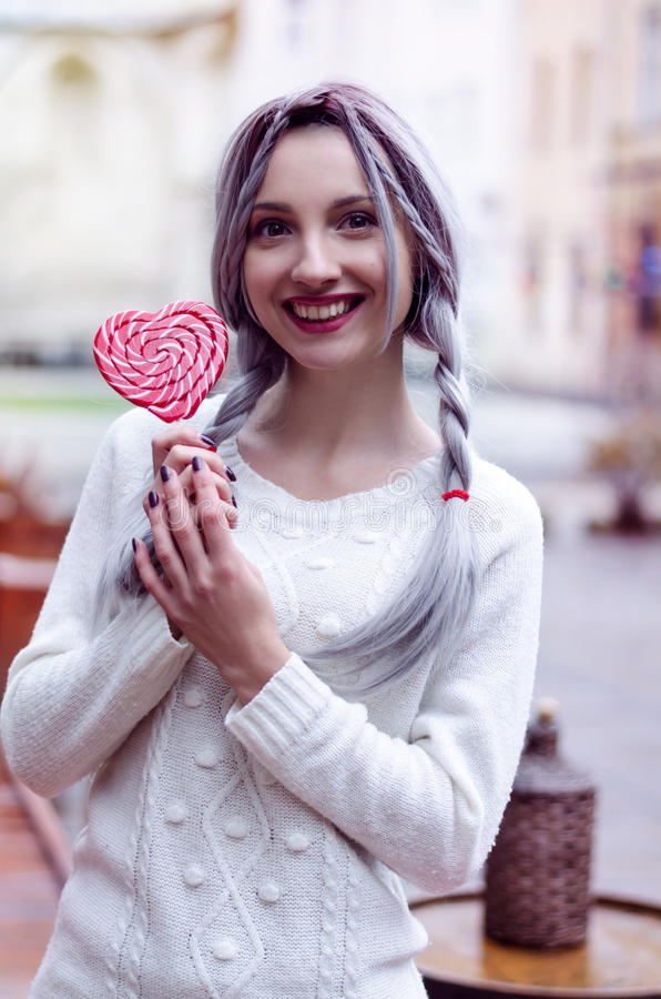 Closeup portrait amazing girl in the white warm woolen sweater with gray silver hair with red and white lollipop stock image