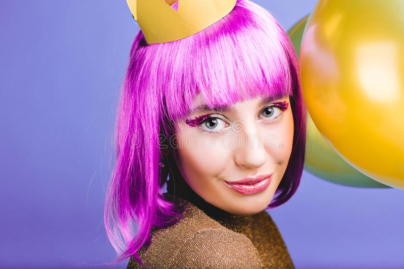 Closeup portrait amazing joyful young woman with cut purple hair, golden crown and balloons celebrating carnival, new stock photos